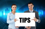 Business partners holding card saying tips against blue bar chart graphic with light