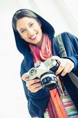 Attractive brunette holding her camera on white background
