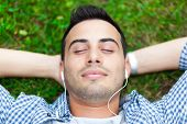 Man listening to music laying on the grass