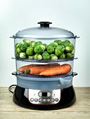 Healthy food in steamer, steam cooker with brussels sprouts and carrots