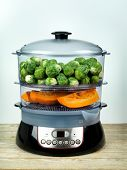 Healthy food in steamer, steam cooker with pumpkin and brussels sprouts
