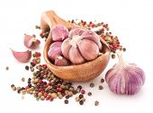 Garlic cloves in wooden bowl isolated on white background