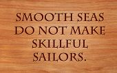 Smooth seas do not make skillful sailors. - African Proverb on wooden red oak background