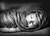 Closeup portrait of adorable newborn girl sleeping at home, black and white photo of little baby wra