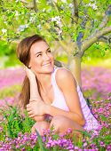 Cheerful smiling female spending time on backyard, looking on side, enjoying apple tree blossom, sit