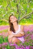 Beautiful calm girl with closed eyes sitting down on pink floral glade under blooming apple tree, re