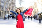 Shopping woman excited happy on La Rambla street in Barcelona. Shopper girl holding shopping bags up