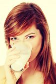Young beautiful teen woman drinking milk