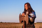 image of armor suit  - Medieval knight in the field with an axe