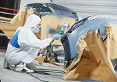 auto mechanic worker painting car bumper at automobile repair and renew service station shop by spra