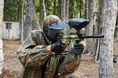 paintball sport player man in protective camouflage uniform and mask with marker gun outdoors