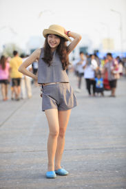 picture of post-teen  - young and pretty asian woman wearing straw hat standing and posting with crowded behind - JPG