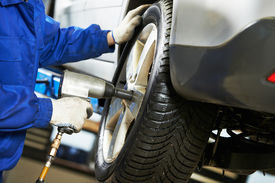 picture of levers  - car mechanic screwing or unscrewing car wheel of lifted automobile by pneumatic wrench at repair service station - JPG