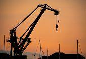 Silhouette dockside crane at sunset