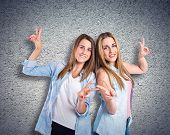 Girls Doing Victory Gesture Over Textured Background