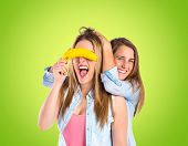 Friends Playing With Fruits Over Green Background