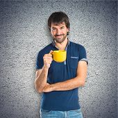 Man Holding A Cup Of Coffee Over Textured Background