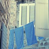 Old Window With Shutters And Blue Washing Linen