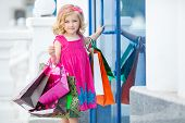 foto of curio  - Cheerful preschool girl walking with shopping bags - JPG