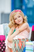 stock photo of curio  - Little fashion girl with packages in a large shopping center - JPG