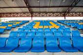 picture of grandstand  - Empty plastic chairs of blue and yellow on grandstand stadium