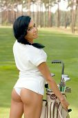 Attractive brunette golfer girl on golf course