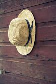 Selective Focus Of Amish Man's Straw Hat On Barn Door