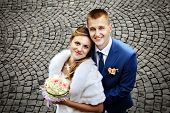 Newlyweds Smiling, View From Above, On A Background Of Cobblestones.
