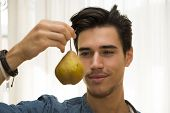 Young Man Holding A Large Ripe Yellow Pear