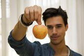 Young Man Holding A Large Delicious Ripe Apple