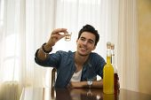 Young Man Sitting Drinking Alone At A Table, Making A Toast