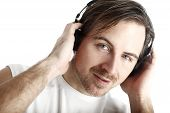 Attractive Man With Headphones In Front Of A White Background Looks Into The Camera