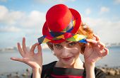 stock photo of clown face  - portrait of a cheerful clown with the red hat on the background of blue sky - JPG
