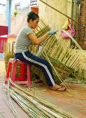 woman making a bamboo basket