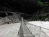 stock photo of nepali  - Traditional Nepali suspension bridge crossing a wild Himalayan river to a trekker - JPG