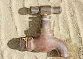 Rustic Water Faucet Tap Lying On Sand