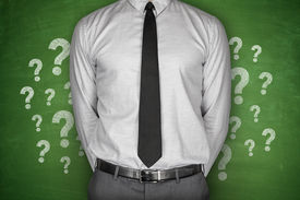 stock photo of punctuation marks  - Question Marks on green Blackboard with businessman - JPG