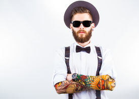 image of bowing  - young hipster man wearing hat suspenders bow - JPG