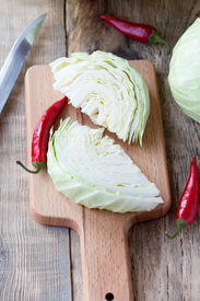 pic of cruciferous  - Cutted cabbage on cutting board with red chili peppers and knife on wooden background - JPG