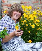 Happy Moddle Aged Woman Working In Her Backyard Garden