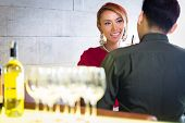 Asian couple drinking white wine in fancy bar