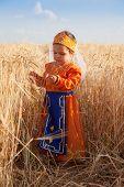 Little Girl In A National Armenian Dress Costs Among Wheat Field