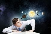 Young businessman leaning on table and planets of space spinning around