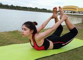 Young Woman Doing Yoga Exercise In The Park
