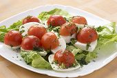 Mozzarella Cheese With Tomatoes On A Green Lettuce