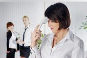 Upset business lady with phone tube in office