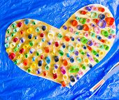 Colorful Paper Heart Hand Made From Rolled Up Pieces On Blue Background Photo