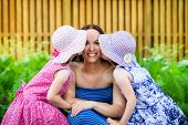Daughters Kissing Their Mother On The Cheek