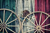 foto of red siding  - A close up of two antique wagon wheels lying up against a building with wooden siding depicting the flag of Mexico on its surface - JPG