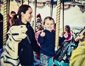 stock photo of amusement park rides  - A happy mother and son are riding on a carousel together smiling and having fun at an amusement park - JPG